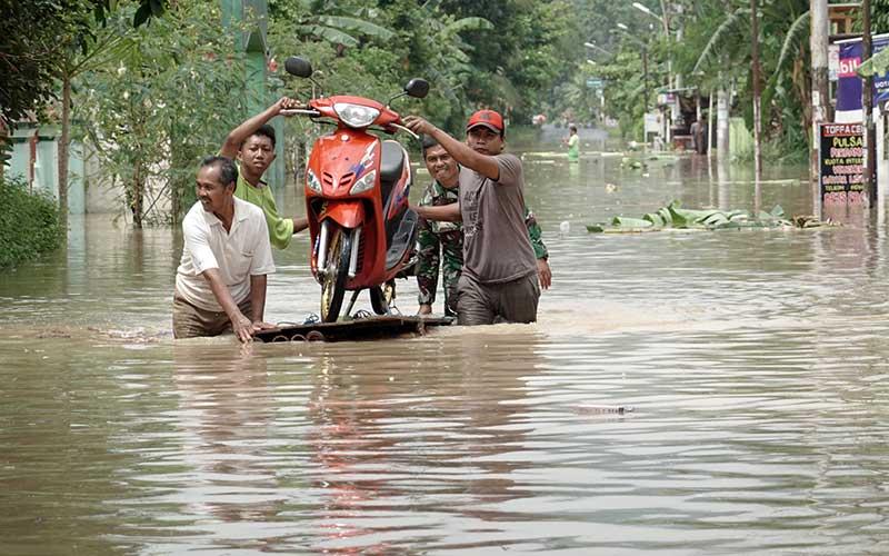 Warga memindahkan motor roda dua dari kawasan terendam banjir menggunakan rakit darurat di Desa Kalisube, Kecamatan Banyumas, Banyumas, Jawa Tengah, Kamis (3/12/2020). Sejumlah wiayah di Kabupaten Banyumas mengalami longsor dan banjir akibat curah hujan ekstrim pada Rabu (2/12) malam dan menyebabkan Sungai Serayu meluap sehingga merendam permukiman di sekitar aliran sungai Serayu di Kabupaten Banyumas. ANTARAFOTO/Idhad Zakaria