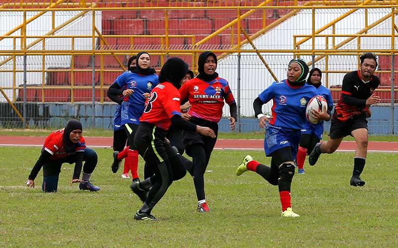 Pemain putri cabor Rugby PON Aceh membawa bola saat melewati pemain putri Rugby Barbarian pada pertandingan eksebisi di stadion Harapan Bangsa, Banda Aceh, Aceh, Sabtu (5/12/2020). Tim Rugby PON Aceh berhasil mengalahkan tim putri Rugby Barbarian dengan skor 19-7. ANTARA FOTO/Irwansyah Putra