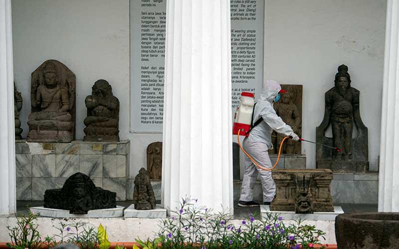 Petugas Palang Merah Indonesia (PMI) menyemprotkan cairan disinfektan di Museum Nasional, Jakarta, Sabtu (5/12/2020). Penyemprotan disinfektan tersebut terus dilakukan secara berkala untuk mencegah penyebaran virus corona saat museum tersebut dibuka untuk wisatawan. ANTARA FOTO/Aditya Pradana Putra