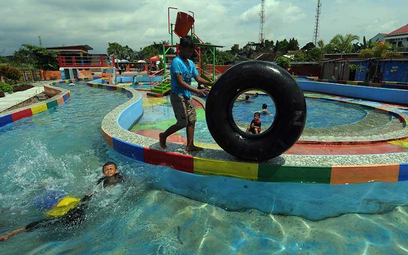 Sejumlah pengunjung berenang dan bermain air di waterpark Umbul Pluneng, Kebonarum, Klaten, Jawa Tengah, Sabtu (5/12/2020). Otoritas Jasa Keuangan (OJK) telah menginisiasi pengembangan Badan Usaha Milik Desa (BUMDes) melalui program BUMDes Center yang kini telah terbentuk 29 BUMDes Center di Sumatra Selatan, Kalimantan Timur, Jawa, Nusa Tenggara Timur, dan Papua sebagai upaya menumbuhkan perekonomian daerah. ANTARA FOTO/Aloysius Jarot Nugroho