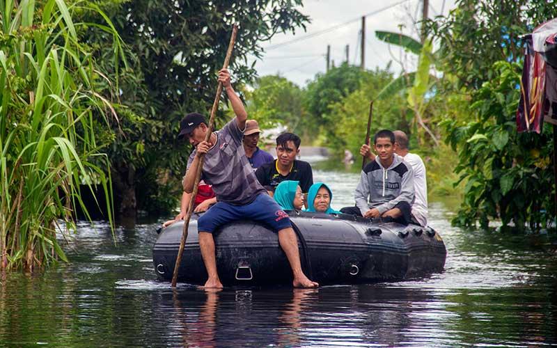 Relawan menggunakan perahu karet  mengevakuasi warga yang terdampak banjir di Desa Banua Raya, Kabupaten Tanah Laut, Kalimantan Selatan, Senin (11/1/2021). Berdasarkan data yang telah di himpun aparat desa Banua Raya, sebanyak 2.907 Jiwa terdampak banjir akibat luapan sungai Bati Bati. ANTARA FOTO/Bayu Pratama S