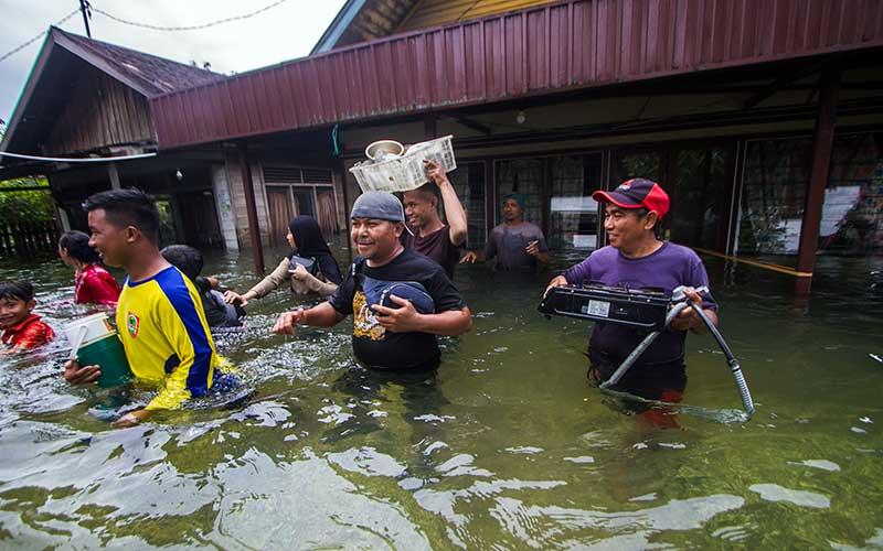 Warga menyelamatkan barang dari rumah yang terendam banjir di Desa Banua Raya di Kabupaten Tanah Laut, Kalimantan Selatan, Senin (11/1/2021). Berdasarkan data yang telah di himpun aparat desa Banua Raya, sebanyak 2.907 Jiwa terdampak banjir akibat luapan sungai Bati Bati. ANTARA FOTO/Bayu Pratama S