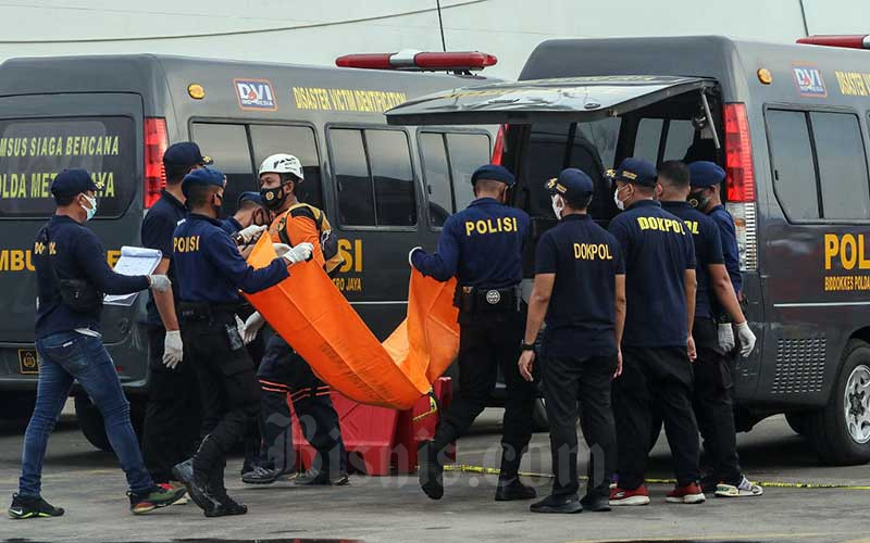 Petugas membawa kantong jenazah berisi bagian tubuh korban pesawat Sriwijaya Air SJ 182 rute Jakarta - Pontianak yang hilang kontak di perairan Pulau Seribu, di Dermaga JICT, Jakarta, Senin (11/1/2021). Hingga pukul 17.00 WIB pada hari ketiga pencarian korban Sriwijaya Air SJ 182, tim Badan SAR Nasional (Basarnas) telah mengumpulkan 40 kantong jenazah yang selanjutnya akan di bawa ke RS Polri untuk dilakukan identifikasi. Bisnis/Eusebio Chrysnamurti
