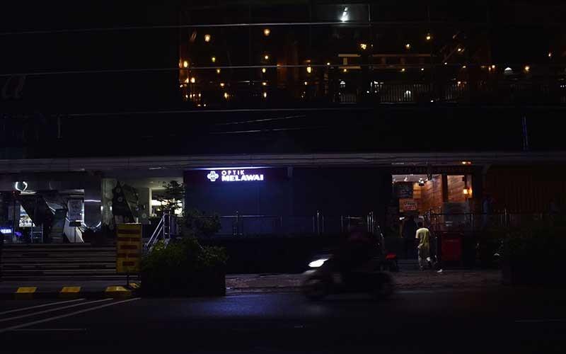 Pengendara melaju di depan sebuah plaza saat diberlakukan Pelaksanaan Pembatasan Kegiatan Masyarakat (PPKM) di Kota Madiun, Jawa Timur, Senin (11/1/2021) malam. Pemkot Madiun memenerapkan PPKM antara lain dengan memadamkan lampu penerangan jalan umum di sejumlah kawasan mulai pukul 19.00, mengatur jam buka plaza hingga hingga pukul 19.00, dan rumah makan, warung, pedagang kaki lima serta toko hingga pukul 21.00 guna pencegahan penularan Covid-19. ANTARA FOTO/Siswowidodo