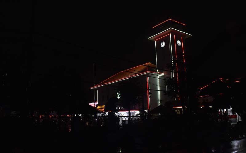 Suasana kawasan Balai Kota Madiun tanpa lampu penerangan jalan umum saat diberlakukan Pelaksanaan Pembatasan Kegiatan Masyarakat (PPKM) di Kota Madiun, Jawa Timur, Senin (11/1/2021) malam. Pemkot Madiun memenerapkan PPKM antara lain dengan memadamkan lampu penerangan jalan umum di sejumlah kawasan mulai pukul 19.00, mengatur jam buka plaza hingga hingga pukul 19.00, dan rumah makan, warung, pedagang kaki lima, serta toko hingga pukul 21.00 guna pencegahan penularan Covid-19. ANTARA FOTO/Siswowidodo