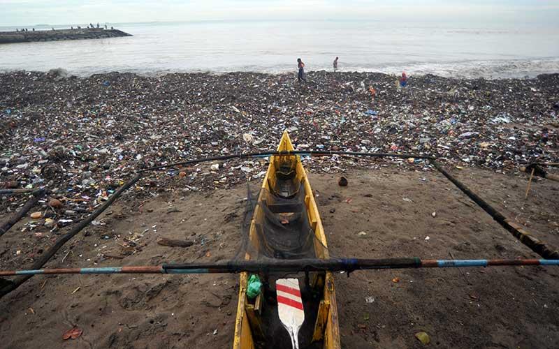Anak-anak melintas di depan perahu nelayan yang terhambat sampah di Pantai Muaro Lasak, Padang, Sumatera Barat, Selasa (12/1/2020). Nelayan Muaro Lasak mengeluhkan sudah empat hari tidak bisa pergi melaut karena terhambat sampah yang menumpuk di pantai. ANTARA FOTO/Iggoy el Fitra