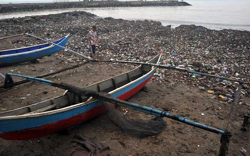 Nelayan melihat kondisi perahunya yang terhambat sampah di Pantai Muaro Lasak, Padang, Sumatera Barat, Selasa (12/1/2020). Nelayan Muaro Lasak mengeluhkan sudah empat hari tidak bisa pergi melaut karena terhambat sampah yang menumpuk di pantai. ANTARA FOTO/Iggoy el Fitra