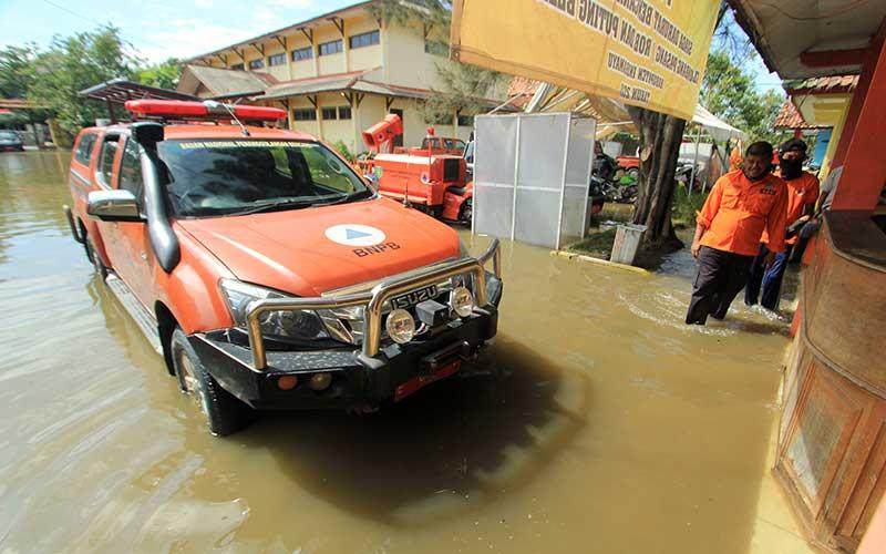 Petugas berada di sekitar kantor BPBD yang terendam banjir di Indramayu, Jawa Barat, Selasa (12/1/2021). Banjir tersebut akibat buruknya drainase dan tingginya intensitas hujan yang terjadi di wilayah Indramayu dan sekitarnya. ANTARA FOTO/Dedhez Anggara