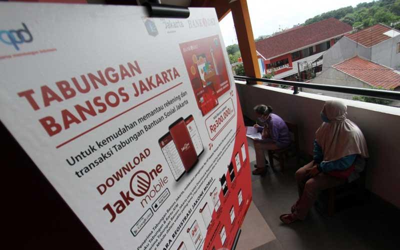 Warga mengantre membuka tabungan Bansos Bank DKI Jakarta di Jakarta, Selasa (12/1/2021). Dinas Sosial DKI Jakarta bersama Bank DKI mulai menyalurkan Bantuan Sosial Tunai (BST) Pemprov DKI Jakarta secara bertahap dengan penerapan protokol kesehatan yang ketat. Besaran BST DKI Jakarta sebesar Rp300 ribu per bulannya yang diberikan selama empat bulan, mulai dari bulan Januari hingga April 2021.Bisnis