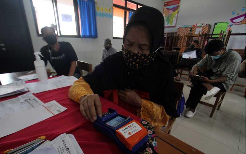 Penerima manfaat melakukan registrasi pin kartu ATM yang merupakan bagian dari tabungan Bansos Jakarta di Jakarta, Selasa (12/1/2021). Dinas Sosial DKI Jakarta bersama Bank DKI mulai menyalurkan Bantuan Sosial Tunai (BST) Pemprov DKI Jakarta secara bertahap dengan penerapan protokol kesehatan yang ketat. Besaran BST DKI Jakarta sebesar Rp300 ribu per bulannya yang diberikan selama empat bulan, mulai dari bulan Januari hingga April 2021.Bisnis