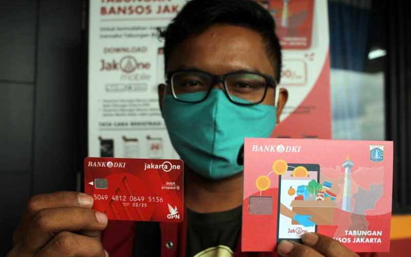Warga menunjukan tabungan Bansos Bank DKI Jakarta di Jakarta, Selasa (12/1/2021). Dinas Sosial DKI Jakarta bersama Bank DKI mulai menyalurkan Bantuan Sosial Tunai (BST) Pemprov DKI Jakarta secara bertahap dengan penerapan protokol kesehatan yang ketat. Besaran BST DKI Jakarta sebesar Rp300 ribu per bulannya yang diberikan selama empat bulan, mulai dari bulan Januari hingga April 2021.Bisnis