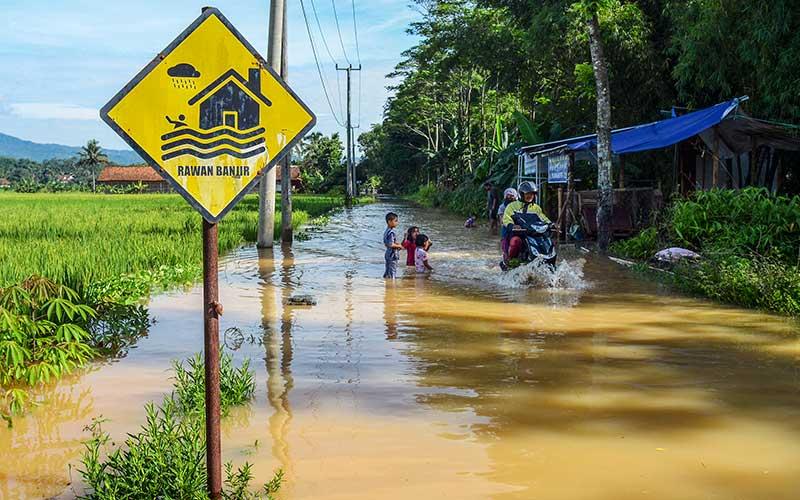 Pengendara menerobos banjir yang merendam jalan di Desa Tanjungsari, Kecamatan Sukaresik, Kabupaten Tasikmalaya, Jawa Barat, Selasa (13/1/2021). Akibat intensitas curah hujan yang tinggi, air Sungai Citanduy dan Cikidang meluap dan merendam puluhan rumah dan 21 hektare lahan pertanian setinggi 30-60 sentimeter. ANTARA FOTO/Adeng Bustomi