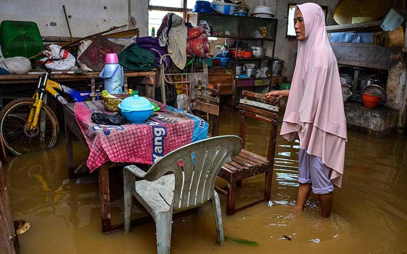 Seorang ibu berjalan di dalam rumahnya yang terendam banjir di Desa Tanjungsari, Kecamatan Sukaresik, Kabupaten Tasikmalaya, Jawa Barat, Selasa (13/1/2021). Akibat intensitas curah hujan yang tinggi, air Sungai Citanduy dan Cikidang meluap dan merendam puluhan rumah dan 21 hektare lahan pertanian setinggi 30-60 sentimeter. ANTARA FOTO/Adeng Bustomi