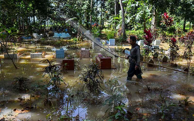 Warga mencari ikan di Tempat Pemakaman Umum (TPU) yang terendam banjir di Desa Tanjungsari, Kecamatan Sukaresik, Kabupaten Tasikmalaya, Jawa Barat, Rabu (13/1/2021). Akibat intensitas curah hujan yang tinggi, air Sungai Citanduy dan Cikidang meluap dan merendam puluhan rumah dan 21 hektare lahan pertanian setinggi 30-60 sentimeter. ANTARA FOTO/Adeng Bustomi