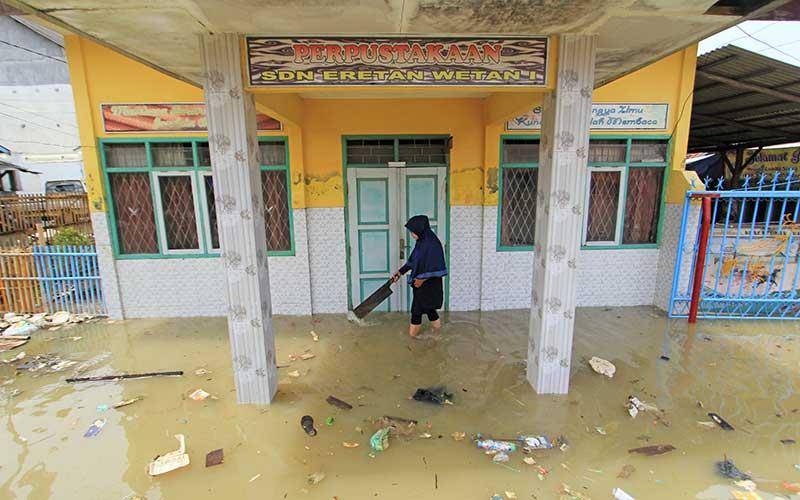 Seorang guru membersihkan sampah di sekitar ruang perpustakaan SDN Eretan Wetan 1 yang terendam banjir rob di Kandanghaur, Indramayu, Jawa Barat, Rabu (13/1/2021). Banjir rob akibat pasang air laut itu merendam ratusan rumah warga, bangunan sekolah dan mushola di kecamatan itu. ANTARA FOTO/Dedhez Anggara