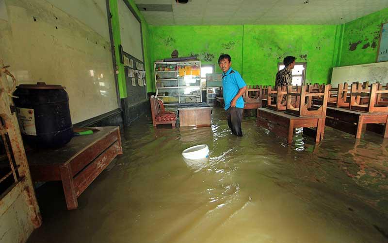 Dua orang guru menyelamatkan barang di ruang kelas SDN Eretan Wetan 1 yang terendam banjir rob di Kandanghaur, Indramayu, Jawa Barat, Rabu (13/1/2021). Banjir rob akibat pasang air laut itu merendam ratusan rumah warga, bangunan sekolah dan mushola di kecamatan itu. ANTARA FOTO/Dedhez Anggara