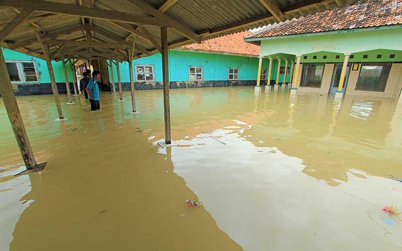 Seorang guru melihat banjir rob yang merendam bangunan SDN Eretan Wetan 1 di Kandanghaur, Indramayu, Jawa Barat, Rabu (13/1/2021). Banjir rob akibat pasang air laut itu merendam ratusan rumah warga, bangunan sekolah dan mushola di kecamatan itu. ANTARA FOTO/Dedhez Anggara