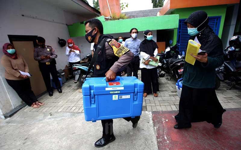 Petugas pengelola vaksin didampingi polisi membawa kotak pendingin berisi vaksin Covid-19 Sinovac saat pendistribusian di Instalasi Farmasi Dinas Kesehatan Kota Bandung, Jawa Barat, Rabu (13/1/2021). Dinas Kesehatan Kota Bandung mendistribusikan 25.000 dosis vaksin Covid-19 ke 191 fasilitas kesehatan di Kota Bandung, untuk pelaksanaan vaksinasi Covid-19 tahap pertama bagi sumber daya manusia (SDM) di lingkungan kesehatan, kepala daerah serta tokoh publik pada 14 Januari 2021. Bisnis/Rachman
