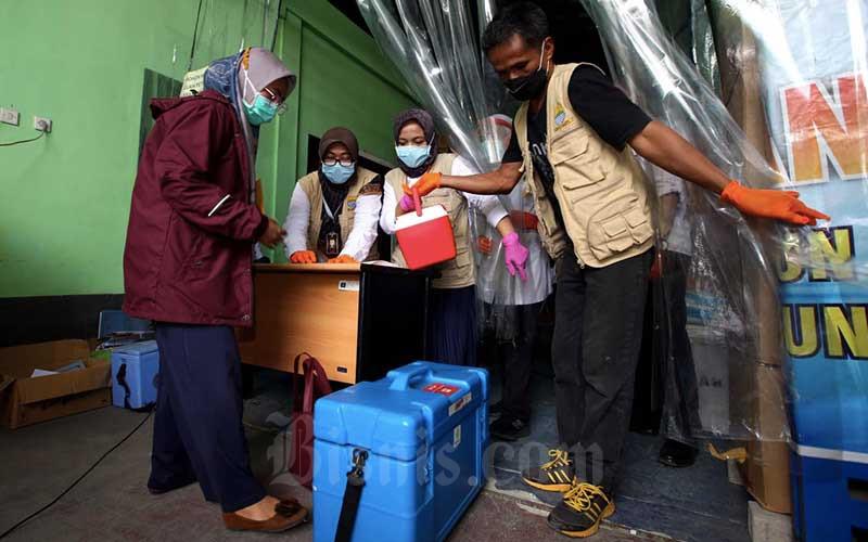 Petugas kesehatan memeriksa kotak pendingin untuk membawa vaksin saat pendistribusian vaksin Covid-19 Sinovac di Instalasi Farmasi Dinas Kesehatan Kota Bandung, Jawa Barat, Rabu (13/1/2021). Dinas Kesehatan Kota Bandung mendistribusikan 25.000 dosis vaksin Covid-19 ke 191 fasilitas kesehatan di Kota Bandung, untuk pelaksanaan vaksinasi Covid-19 tahap pertama bagi sumber daya manusia (SDM) di lingkungan kesehatan, kepala daerah serta tokoh publik pada 14 Januari 2021. Bisnis/Rachman