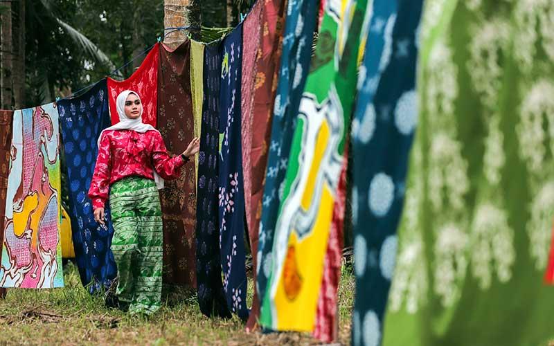Wisatawan mengamati kain tenun khas Batam yang dijemur di Rumah Tenun  Pulau Ngenang, Batam , Kepulauan Riau, Rabu (13/1/2021).  Selain sebagai mata pencarian, warga setempat menjadikan produksi kain tenun khas Batam sebagai salah satu objek wisata di pulau tersebut. ANTARA FOTO/Teguh prihatna