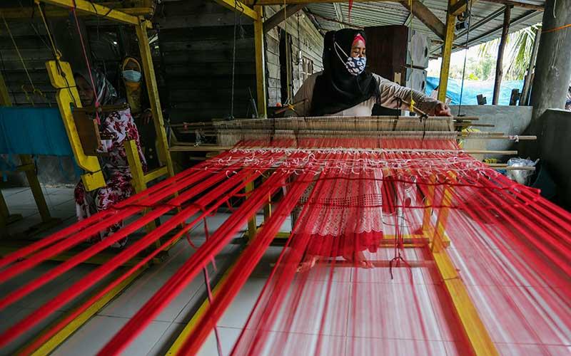 Perajin membuat kain tenun mengunakan Alat Tenun Bukan Mesin (ATBM) di Rumah Tenun  Pulau Ngenang, Batam , Kepulauan Riau, Rabu (13/1/2021). Selain sebagai mata pencarian, warga setempat menjadikan produksi kain tenun khas Batam sebagai salah satu objek wisata di pulau tersebut. ANTARA FOTO/Teguh prihatna