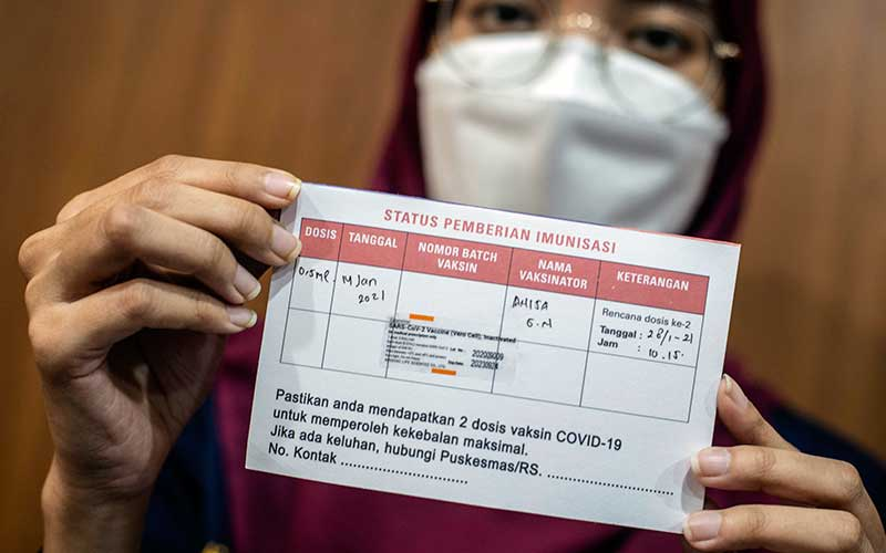Tenaga kesehatasan menunjukkan kartu vaksinasi Covid-19 seusai disuntik vaksin CoronaVac di Puskesmas Cilincing, Jakarta, Kamis (14/1/2021). Tenaga kesehatan di wilayah Pemprov DKI Jakarta mulai disuntik vaksin Covid-19 buatan perusahaan farmasi Sinovac asal China. ANTARA FOTO/Aprillio Akbar