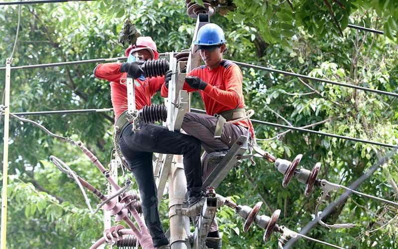 Teknisi mengerjakan perbaikan jaringan kelistrikan di Makassar, Sulawesi Selatan, Kamis (14/1/2021). Biaya pokok penyediaan (BPP) tenaga listrik sepanjang 2020 mengalami penurunan hingga Rp41,91 triliun. BPP listrik turun menjadi Rp317,12 triliun dari perkiraan awal sebesar Rp359,03 triliun. Bisnis/Paulus Tandi Bone
