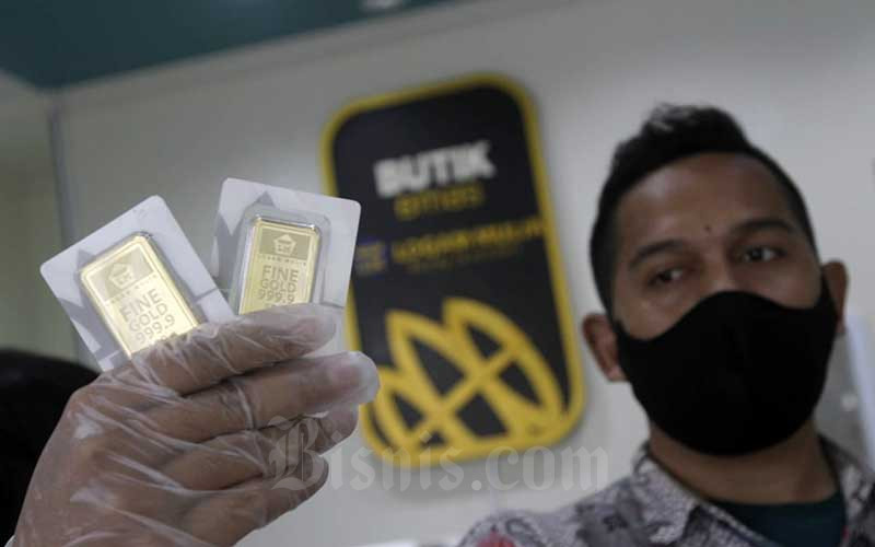 Karyawan menunjukan emas logam mulia di Butik Antam, Jakarta, Kamis (14/1/2021). Berdasarkan informasi dari Unit Bisnis Pengolahan dan Pemurnian Logam Mulia Antam, harga emas 24 karat pada Kamis (14/1/2021) untuk ukuran 1 gram senilai Rp955.000 per gram, naik Rp10.000 dibanding hari sebelumnya. Adapun emas satuan terkecil dengan ukuran 0,5 gram dibanderol Rp537.500, turun Rp5.000 dibandingkan dengan posisi hari sebelumnya. Bisnis/Himawan L Nugraha