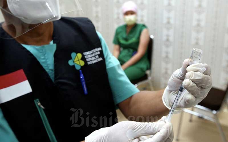 Vaksinator memasukkan cairan vaksin Covid-19 Sinovac ke dalam suntikan yang akan disuntikan kepada tenaga kesehatan (nakes) di Rumah Sakit Hasan Sadikin (RSHS), Bandung, Jawa Barat, Kamis (14/1/2021). Dinas Kesehatan Kota Bandung mencatat sebanyak 5.200 nakes menjalani vaksinasi Covid-19 tahap I termin I yang dilaksanakan pada Kamis (14/1/21) secara serentak di sejumlah fasilitas kesehatan yang tersebar dibeberapa wilayah di Kota Bandung. Bisnis/Rachman