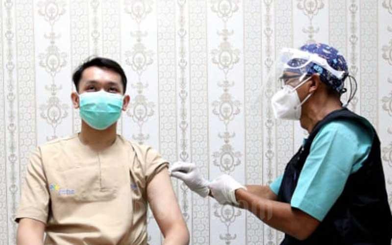Vaksinator menyuntikan vaksin Covid-19 Sinovac kepada salah seorang tenaga kesehatan (nakes) di Rumah Sakit Hasan Sadikin (RSHS), Bandung, Jawa Barat, Kamis (14/1/2021). Dinas Kesehatan Kota Bandung mencatat sebanyak 5.200 nakes menjalani vaksinasi Covid-19 tahap I termin I yang dilaksanakan pada Kamis (14/1/21) secara serentak di sejumlah fasilitas kesehatan yang tersebar dibeberapa wilayah di Kota Bandung. Bisnis/Rachman