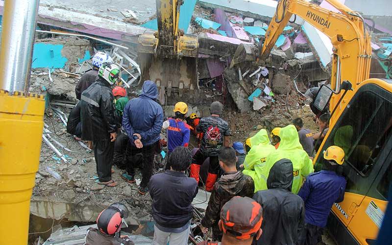 Petugas mengevakuasi korban yang terjepit dari bangunan di rumah sakit Mitra Manakarra yang runtuh akibat gempa bumi di Mamuju, Sulawesi Barat, Kamis (15/1/2021). Sebanyak tujuh korban berhasil dievakuasi, empat diantaranya selamat dan tiga lainnya meninggal dunia di reruntuhan rumah sakit tersebut. ANTARA FOTO/ Akbar Tado