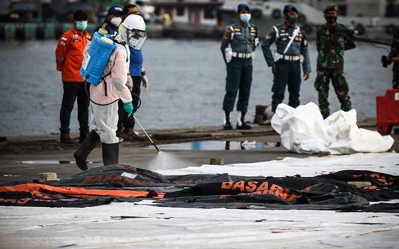 Petugas menyemprotkan cairan disinfektan pada kantong jenazah berisi objek temuan dari lokasi jatuhnya pesawat Sriwijaya Air nomor penerbangan SJ 182 rute Jakarta-Pontianak di Dermaga JICT, Tanjung Priok, Jakarta, Sabtu (16/1/2021). Operasi SAR tersebut memasuki hari kedelapan. ANTARA FOTO/Rivan Awal Lingga