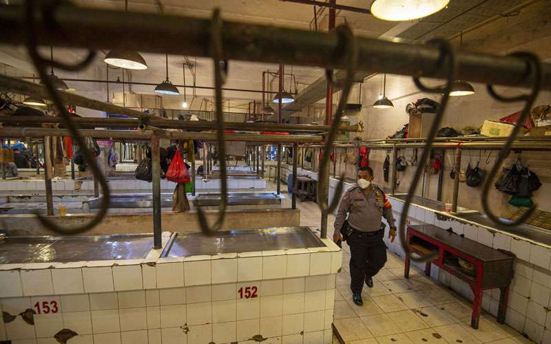 Polisi berjalan di los daging yang sepi akibat aksi mogok pedagang di Pasar Senen, Jakarta, Rabu (20/1/2021). Para pedagang daging sapi di sejumlah pasar di kawasan Jakarta, Bogor, Depok, Tangerang, dan Bekasi (Jabodetabek) menggelar aksi mogok jualan mulai Rabu hingga Jumat (22/1) sebagai bentuk protes kepada pemerintah atas tingginya harga daging sapi yang sudah berlangsung sejak akhir 2020. Saat ini harga daging sapi mencapai sekitar Rp130 ribu per kilogram. ANTARA FOTO/Aditya Pradana Putra