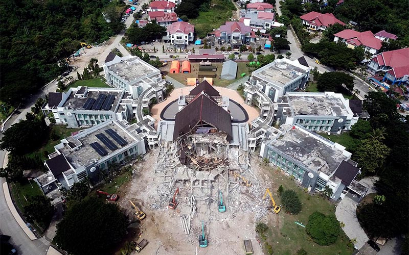 Foto udara memperlihatkan sejumlah alat berat membersihkan reruntuhan bangunan kantor gubernur Sulawesi Barat yang runtuh akibat gempa di Mamuju, Sulawesi Barat, Rabu (20/1/2021). Saat ini pemerintah melakukan perbaikan infrastruktur seperti jaringan listrik, jalan dan fasilitas umum lainnya. Bisnis/Paulus Tandi Bone.