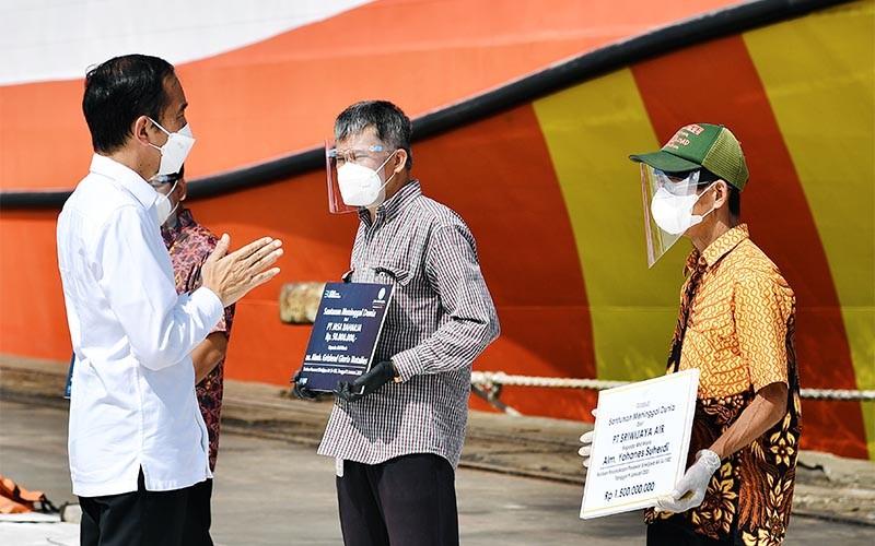 Presiden Joko Widodo (kiri) berbincang dengan sejumlah ahli waris dari korban kecelakaan pesawat Sriwijaya Air PK-CLC nomor penerbangan SJ 182 rute Jakarta-Pontianak di Posko Darurat Evakuasi di Dermaga JICT II, Pelabuhan Tanjung Priok, Jakarta, Rabu (20/1/2021). Presiden juga turut menyaksikan penyerahan santunan sebesar Rp50 juta oleh Jasa Raharja kepada 3 perwakilan penerima yang diwakili oleh para ahli waris. Selain itu, turut pula diserahkan ganti rugi dari pihak Sriwijaya Air kepada salah satu perwakilan penerima dengan nilai Rp1,25 miliar. ANTARA FOTO/Setpres/Laily Rachev