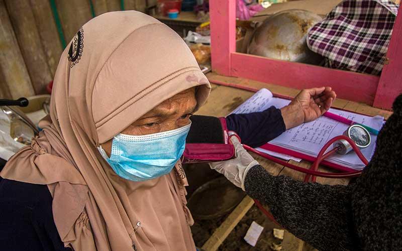 Relawan dari Yayasan KUN Humanity System memeriksa kesehatan warga yang terdampak banjir bandang di Desa Hantakan, Kabupaten Hulu Sungai Tengah, Kalimantan Selatan, Sabtu (23/1/2021). Kegiatan yang dilakukan relawan tdengan mendatangi warga secara langsung ke masing-masing rumah guna memantau kesehatan warga terdampak banjir bandang di Kabupaten Hulu Sungai Tengah. ANTARA FOTO/Bayu Pratama S