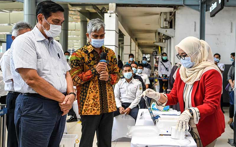 Menteri Koordinator Bidang Kemaritiman dan Investasi, Luhut Binsar Pandjaitan (kiri) didampingi Kepala Produksi Konsorsium GeNose C19 Eko Fajar Prasetyo (tengah) mengamati kantong nafas miliknya saat dites di Stasiun Pasar Senen, Jakarta, Sabtu (23/1/2021). Menteri Perhubungan Budi Karya Sumadi akan mengimplementasikan penggunaaan GeNose C19 sebagai alat pendeteksi Covid-19 pada calon penumpang kereta api mulai 5 Februari 2021. ANTARA FOTO/M Risyal Hidayat