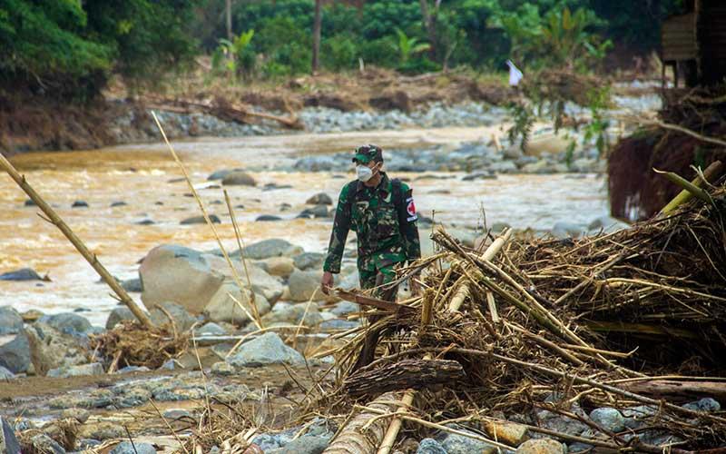 Letda CKM dr Fitriandrirama dari Pusat Kesehatan Angkatan Darat (Puskesad) TNI Angakatan Darat melintasi puing-puing batang pohon yang hanyut akibat banjir bandang di Desa Datar Ajab, Kabupaten Hulu Sungai Tengah, Kalimantan Selatan, Minggu (24/1/2021). Puskesad TNI Angkatan Darat telah memeriksa 400 warga yang menjadi korban banjir hingga menjangkau pedalaman meratus di Kabupaten Hulu Sungai Tengah dalam operasi bantuan penanganan banjir di Kalimantan Selatan. ANTARA FOTO/Bayu Pratama S