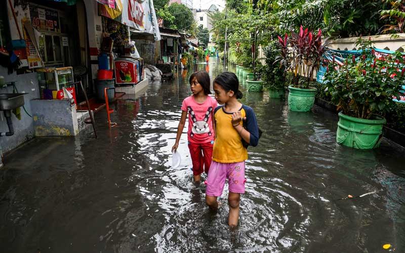 Dua orang bocah berjalan melewati genangan banjir di kawasan Jakarta Selatan, Senin (25/1/2021). Banjir di sejumlah wilayah Ibu Kota disebabkan intensitas hujan yang tinggi serta buruknya drainase. ANTARA FOTO/M Risyal Hidayat