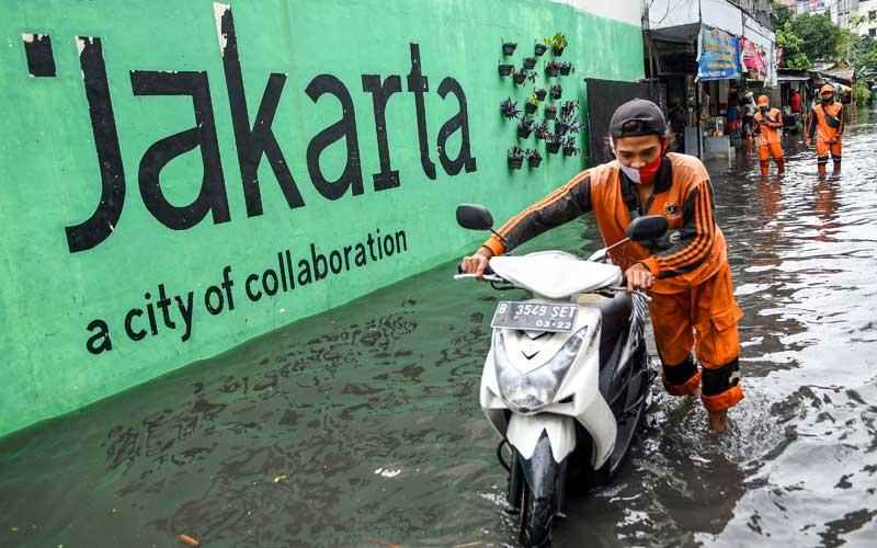 Petugas Penanganan Prasarana dan Sarana Umum (PPSU) menuntun sepeda motor ketika banjir menggenangi kawasan Jakarta Selatan, Senin (25/1/2021). Banjir di sejumlah wilayah Ibu Kota disebabkan intensitas hujan yang tinggi serta buruknya drainase. ANTARA FOTO/M Risyal Hidayat