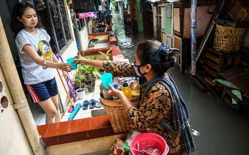 Penjual jamu melayani pembeli di depan rumah yang terendam banjir kawasan Jakarta Selatan, Senin (25/1/2021). Banjir di sejumlah wilayah Ibu Kota disebabkan intensitas hujan yang tinggi serta buruknya drainase. ANTARA FOTO/M Risyal Hidayat