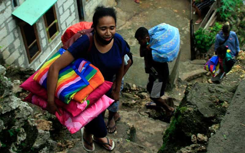 Seorang anak korban tanah longsor menjinjing pakaian dan bantal untuk dibawah ke tempat pengungsian yang disiapkan oleh pemerintah Kota Kupang,di Kota Kupang, NTT, Senin (25/1/2021). Badan Penanggulangan Bencana (BPBD) Kota Kupang mencatat sebanyak 140 warga yang tinggal di dekat lokasi longsor telah mengungsi ke gereja yang telah disiapkan dan tak jauh dari lokasi bencana. ANTARA FOTO/Kornelis Kaha