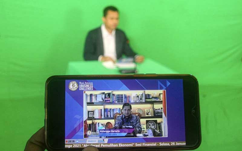 Layar menampilkan Menteri Koordinator Bidang Perekonomian Airlangga Hartarto memberikan pemaparan dalam acara Bisnis Indonesia Business Challenges 2021 di Jakarta, Selasa (26/1/2021). Bisnis/Arief Hermawan P