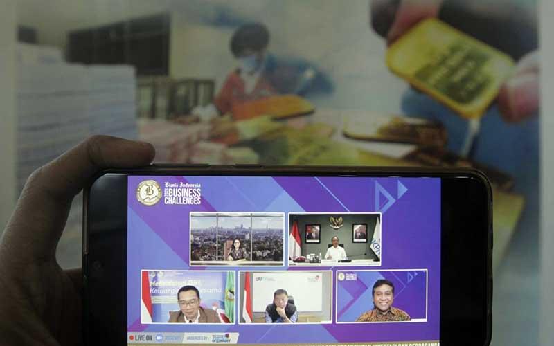 Layar menampilkan Kepala Badan Koordinasi Penanaman Modal (BKPM) Bahlil Lahadalia (kanan atas), Ketua Umum Asosiasi Pengusaha Indonesia (Apindo) Hariyadi B. Sukamdani (kanan bawah), CEO Telkom Indonesia Ririek Adriansyah (tengah bawah), Gubernur Jawa Barat Ridwan Kamil (kiri bawah), dan Pemimpin Redaksi Bisnis Indonesia Maria Y. Benyamin memberikan pemaparan dalam acara Bisnis Indonesia Business Challenges 2021 di Jakarta, Selasa (26/1/2021). Bisnis/Himawan L Nugraha