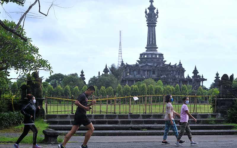 Warga berolahraga di sekitar Lapangan Puputan Margarana yang ditutup di Denpasar, Bali, Selasa (26/1/2021). Pemerintah memperpanjang masa Pemberlakuan Pembatasan Kegiatan Masyarakat (PPKM) di Pulau Jawa dan Bali selama dua pekan hingga 8 Februari mendatang untuk menekan penyebaran Covid-19. ANTARA FOTO/Fikri Yusuf