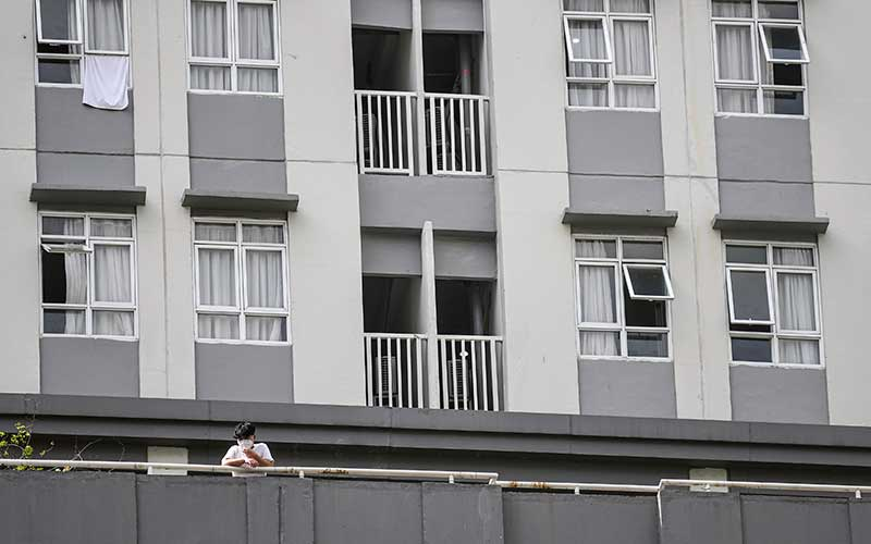 Seorang pasien Covid-19 berdiri di bagian balkon salah satu menara di Rumah Sakit Darurat (RSD) Covid-19, Wisma Atlet Kemayoran, Jakarta, Selasa (26/1/2021). Satuan Tugas Penanganan Covid-19 Pusat mengumumkan per Selasa (26/1) pukul 15.55 WIB, terdapat penambahan jumlah kasus terkonfirmasi positif Covid-19 sebanyak 13.094 orang sehingga total telah mencapai 1.012.350 kasus di Indonesia.  ANTARA FOTO/M Risyal Hidayat/wsj.