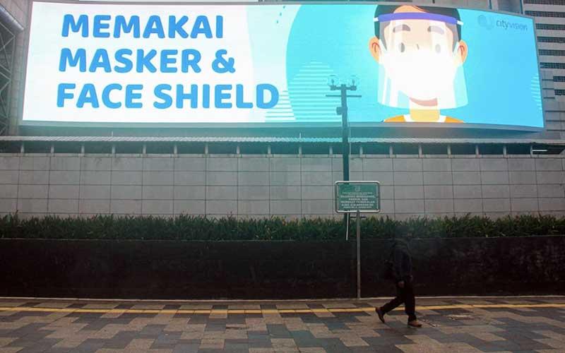 Warga melintas di dekat videotron bertema 3M di Jakarta, Selasa (26/1/2021). Jumlah kasus konfirmasi positif Covid-19 di Indonesia pada Selasa (26/1) tercatat sebanyak 13.094 orang. Dengan penambahan tersebut, secara kumulatif kasus positif di Tanah Air telah mencapai 1.012.350 orang. Bisnis/Arief Hermawan P