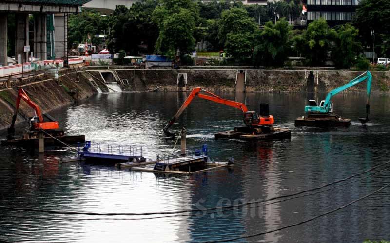 Alat berat mengeruk endapan lumpur di  sungai di Jakarta, Rabu (27/1/2021). Perusahaan pembiayaan PT BFI Finance Indonesia Tbk. (BFI Finance) menargetkan pertumbuhan pembiayaan terkait alat berat pada 2021. Naiknya permintaan alat berat akibat terpantik harga komoditas perkebunan maupun pertambangan, serta kegiatan konstruksi pada tahun ini. Bisnis/Dedi Gunawan