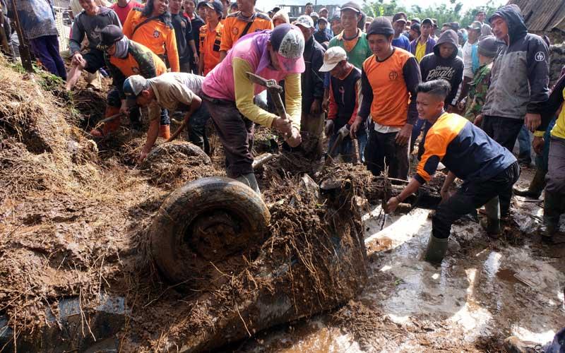 Sejumlah warga bersama relawan menyingkirkan timbunan tanah di lokasi bencana tanah longsor kawasan lereng Gunung Sumbing Dusun Prampelan I, Desa Adipuro, Kaliangkrik, Magelang, Jateng, Rabu (27/1/2021). Akibat hujan lebat sepanjang hari Selasa (26/1/2021) tebing setinggi 25 meter dan lebar 10 meter longsor menyebabkan dua rumah hancur satu rumah rusak ringan, sebuah mobil tertimbun tanah dan empat orang terluka,. ANTARA FOTO/Anis Efizudin