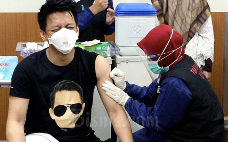Influencer dan musisi asal Bandung Nazril Irham atau Ariel menerima penyuntikan vaksin Covid-19 Sinovac oleh tenaga kesehatan di Rumah Sakit Khusus Ibu dan Anak (RSKIA) Kota Bandung, Jawa Barat, Kamis (28/1/2021). Pejabat Pemerintah Kota Bandung dan beberapa pesohor menjalani vaksinasi vaksin Covid-19 dosis kedua. Para penerima vaksin dosis kedua hari ini mayoritas tidak merasakan efek samping yang mengganggu aktivitasnya. Bisnis/Rachman